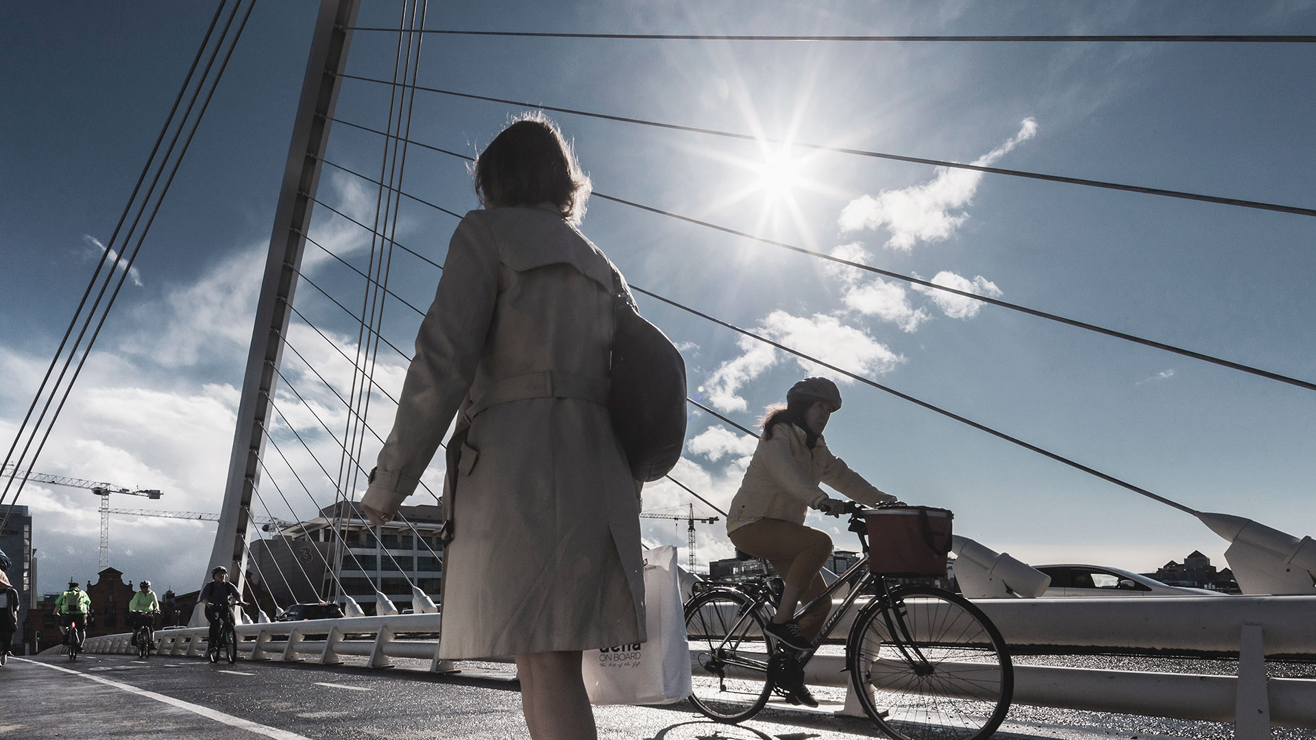 Cyclist and pedestrians cross Samuel Beckett Bridge in Dublin's Docklands